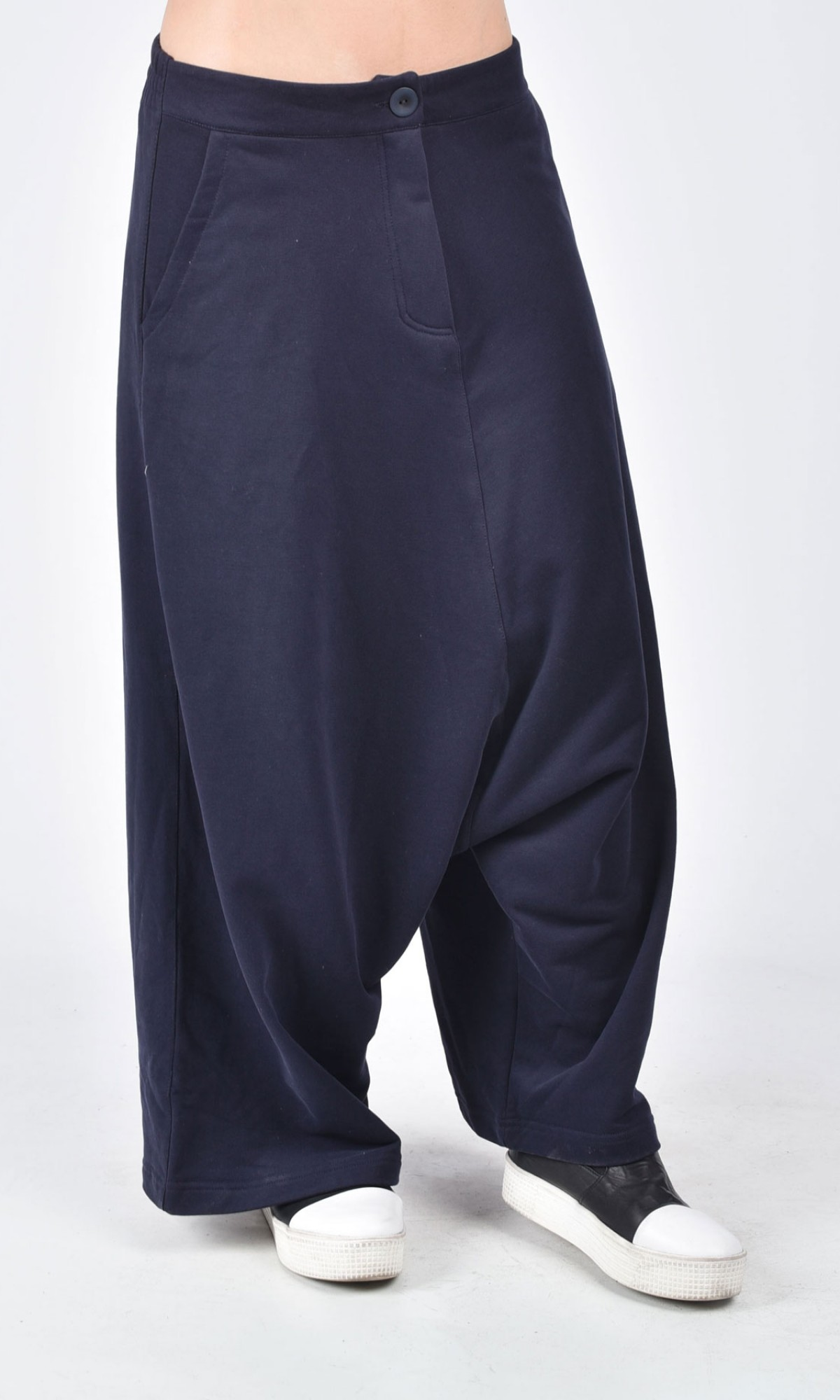 Harem pants feature a dropped crotch that reaches approximately 2 to 3 inches above the knee with an immediate tapered fit down the rest of the leg. Drop crotch pants are easy to wear, comfortable, and flattering for most body types from the loose fit around the hips.